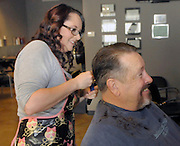 gbs121213j/ASEC -- Audrey Morelock trims the hair of her father, John Morelock, at the Hair Addict salon after cutting off his long hair on Thursday, December 12, 2013.(Greg Sorber/Albuquerque Journal)