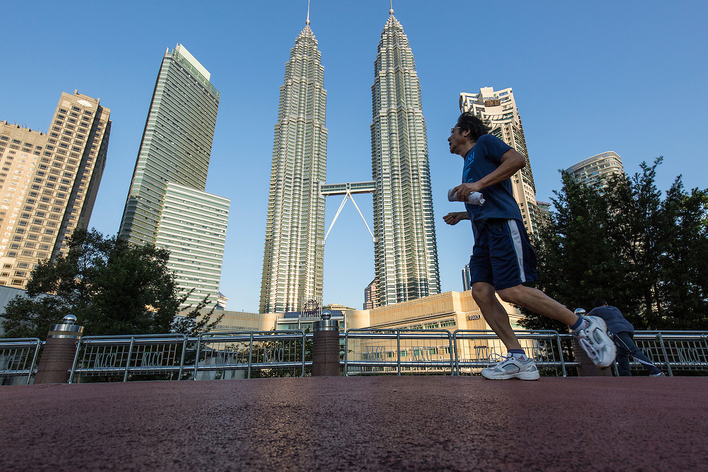 Malaysia, Kuala Lumpur, Low angle view of man jogging on trail in public park beneath 88 story tall Petronas Towers skyscrapers