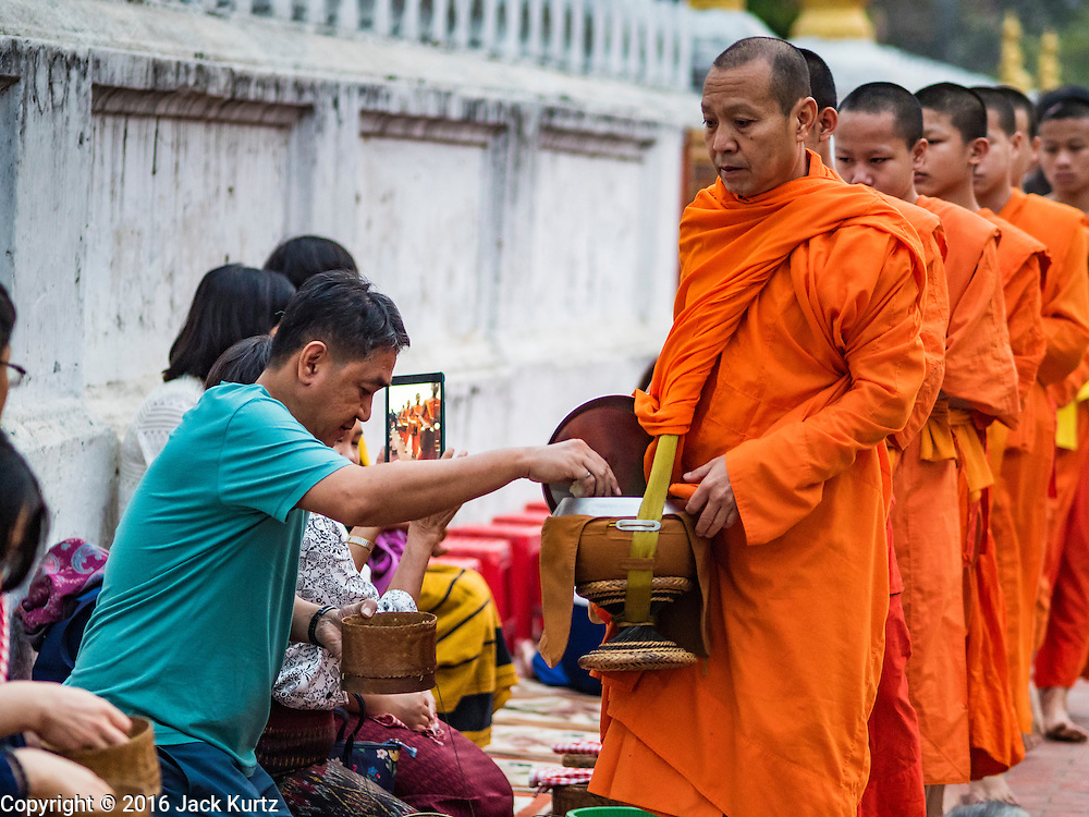 """11 MARCH 2016 - LUANG PRABANG, LAOS:  Tourists give alms to Buddhist monks during the morning tak bat in Luang Prabang. Luang Prabang was named a UNESCO World Heritage Site in 1995. The move saved the city's colonial architecture but the explosion of mass tourism has taken a toll on the city's soul. According to one recent study, a small plot of land that sold for $8,000 three years ago now goes for $120,000. Many longtime residents are selling their homes and moving to small developments around the city. The old homes are then converted to guesthouses, restaurants and spas. The city is famous for the morning """"tak bat,"""" or monks' morning alms rounds. Every morning hundreds of Buddhist monks come out before dawn and walk in a silent procession through the city accepting alms from residents. Now, most of the people presenting alms to the monks are tourists, since so many Lao people have moved outside of the city center. About 50,000 people are thought to live in the Luang Prabang area, the city received more than 530,000 tourists in 2014.      PHOTO BY JACK KURTZ"""