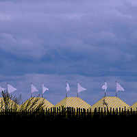 Beach tents stand with flags waving as an autumn storm approaches on the Atlantic Ocean at Cape May, NJ.