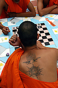 Tattoo Festival at Wat Bang Phra, a Buddhist temple in the town of Nakhorn Chaisri, Thailand - men adorned by Thai Monks with tattoos representing animal spirits often go into a trance claiming they are possessed  by the spirit of the animal. Here Monks take time out to play a board game..March 2003.©David Dare Parker/AsiaWorks Photography