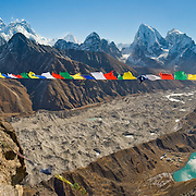 "Prayer flags fly from the trekkers' peak of Gokyo Ri (17,575 feet / 5357 meters elevation). See Mount Everest (center left), adjacent Lhotse, and the distant pyramid of Makalu. The largest glacier in Nepal, Ngozumpa Glacier, flows down the valley floor covered in gray rocks. Its lateral moraine dams several lakes. To the left of Third Gokyo Lake is Gokyo village (15,583 feet / 4750 meters), a small cluster of teahouses for trekkers and climbers. Sagarmatha National Park was created in 1976 and honored as a UNESCO World Heritage Site in 1979. Panorama stitched from 5 images. Published in ""Light Travel: Photography on the Go"" book by Tom Dempsey 2009, 2010."