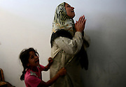 .A young Palestinian girl clings to her mother  durng the funeral of Hamas militant Adel Al-Sakani in the Jabalya refugee camp in Gaza July 7,2006. He was killed by the Israeli Army.