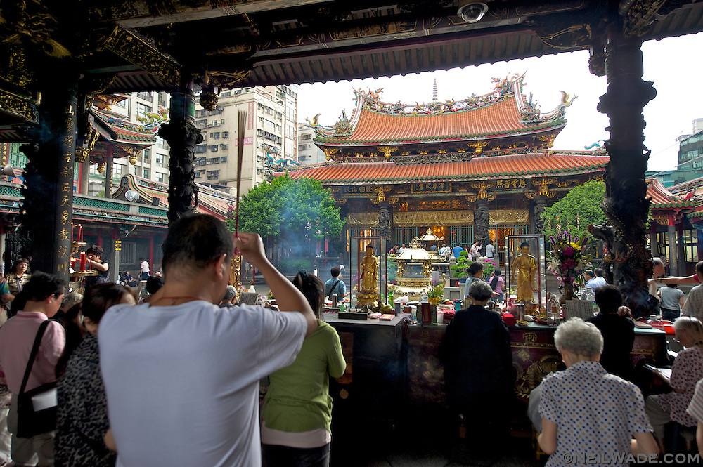 A man prays with incense in his hands as other kneel and recite religious chants inside Longshan Temple.