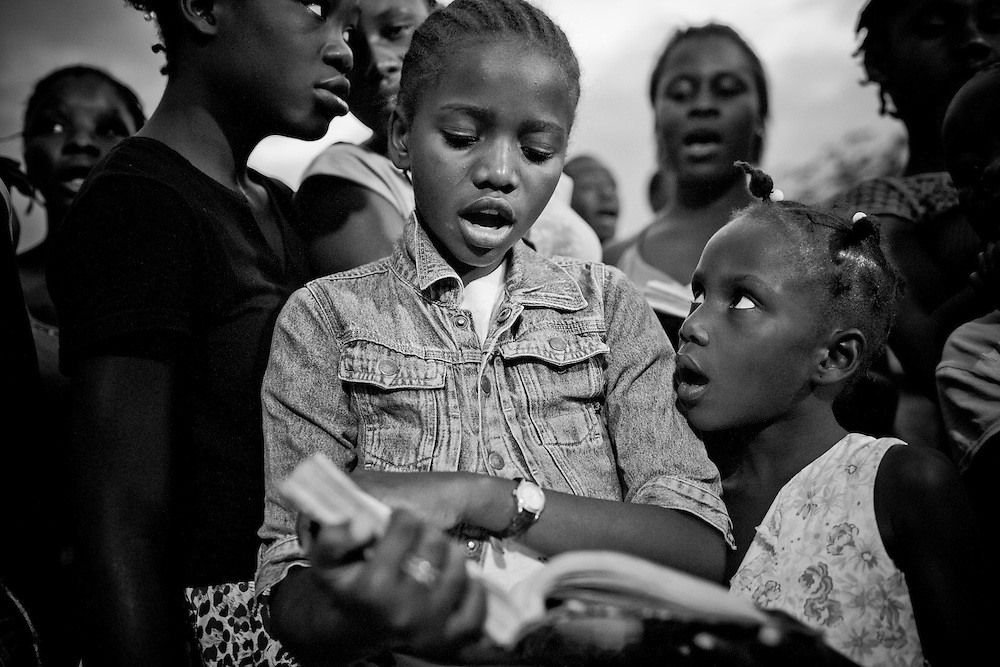 Residents of a camp for those displaced by the recent earthquake pray during an evening church service in Petionville, outside Port-au-Prince, Haiti.