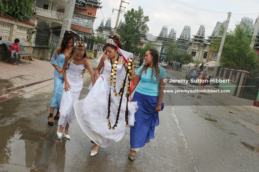 14 year old roma (gypsy) bride Garoafa Mihai walks in the street with her dowry of gold coins, assisted by friends, in Sintesti, Romania, on Sunday, Sept. 24th 2006. Day two of the wedding between Garoafa Mihai, aged 14, and Florin 'Ciprian' Lulu, aged 13, Roma (gypsies) from the village of Sintesti,15 kilometres from Bucharest, Romania. Their partnership was decided by their parents and not through love, and under Romanian law is illegal. The children will neither complete legal paperwork for the wedding, nor visit the local Romanian Orthodox church for a blessing. On her wedding day Garoafa wore approximately 30-40,000 USD of gold Franz Josef coins on her dress, part of the large dowry that she takes with her as she begins her married life. For the guests and for the people of the village another 30,000 USD of pigs, approximately 100,  were killed to be eaten and given away as presents of food. Another 30,000 USD was spent on famous Roma musicians to come and sing 'manele'  type music at the wedding extolling the wealth and status of their patrons for the weekend in their songs.