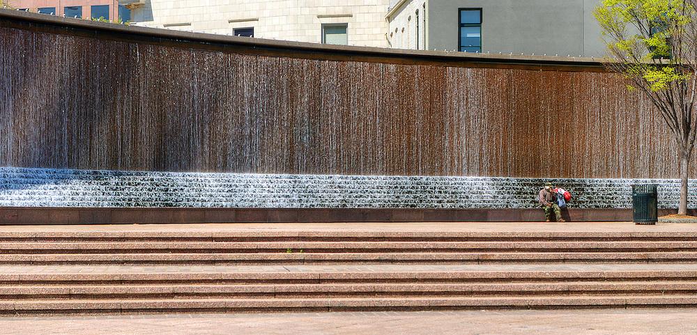 Man sitting near wall of water in downtown Atlanta