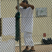 "A detainee covers his face while walking toward his cell in Camp 4 at the Guantanamo Bay detention facility located within the U.S. Naval Station at Guantanamo Bay, Cuba. Camp 4 is a more lenient camp where the most compliant detainees are held in small groups. The U.S. Government is currently holding approximately 340 ""enemy combatants"" in Guantanamo Bay, Cuba. They were captured during the ""Global War on Terrorism"" after the attacks on the United States on September 11, 2001. This photo was reviewed by a U.S. Military official before transmission."