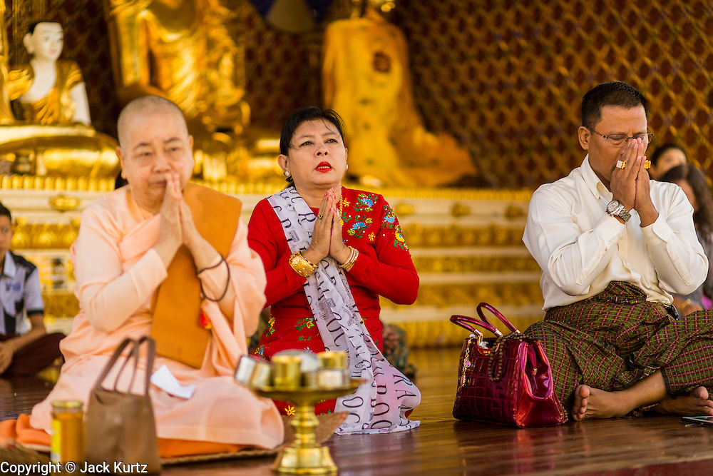 07 JUNE 2014 - YANGON, YANGON REGION, MYANMAR:  People pray at Shwedagon Pagoda in Yangon. Shwedagon Pagoda is officially called Shwedagon Zedi Daw and is also known as the Great Dagon Pagoda and the Golden Pagoda. It's a 99 metres (325 ft) gilded pagoda and stupa located in Yangon. It is the most sacred Buddhist pagoda in Myanmar with relics of the past four Buddhas enshrined within: the staff of Kakusandha, the water filter of Koṇāgamana, a piece of the robe of Kassapa and eight strands of hair from Gautama, the historical Buddha.   PHOTO BY JACK KURTZ