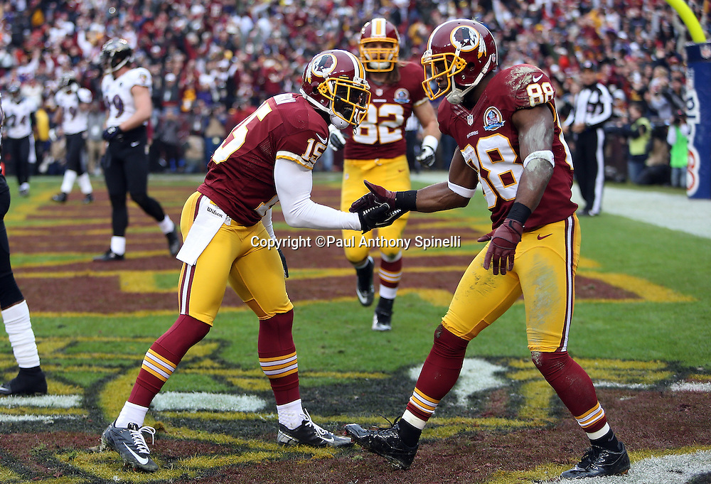Washington Redskins wide receiver Josh Morgan (15) celebrates with a low five from Washington Redskins wide receiver Pierre Garcon (88) after Morgan catches a first quarter touchdown pass that gives the Redskins a 7-0 lead during the NFL week 14 football game against the Baltimore Ravens on Sunday, Dec. 9, 2012 in Landover, Md. The Redskins won the game in overtime 31-28. ©Paul Anthony Spinelli