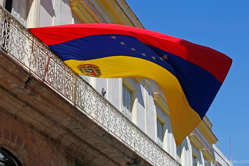 Central America, Cuba, Havana. Venezuela flag flies from balcony in Havana, Cuba.