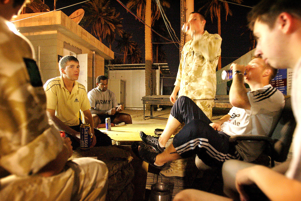 Baghdad, Iarq, 2 Oct 2005. Running 'Route Irish'.....After a daily briefing the troops have access to the ?Mosquito and Camel? bar where they watch TV or play pool and in accordance with the ?2 can rule? are allowed to drink 2 beers per night...B Company, 1st Battalion, The Royal Irish Regiment, a tight-knit multi national fighting force make daily escorting runs along ?Route Irish?, the infamous Baghdad Airport road. The 46 man team are all British Army regulars but come from as far afield as Fiji, South Africa and Northern and Southern Ireland. Previous deployments in Kosovo, Sierra Leone and Northern Ireland have equipped them with the valuable skills needed to provide protection for British Forces and materials transiting the world?s most dangerous highway. Due to an increased presence of US forces along the route both in dug in positions and mobile patrols, attacks along the road have slackened, despite this a day rarely passed without an IED (improvised explosive device) being detonated or a small arms attack against coalition forces. ..The convoy attempts to maintain a seclusion ?bubble? around its vehicles for the duration of the journey. Any civilian vehicle that either strays into the bubble or refuses to keep their distance represents a threat and should they ignore the warning blasts on air horns carried in each vehicle the rules of engagement progress from warning shots to use of lethal force. The relative safety of the International Zone offers them an opportunity to decompress between missions. A duty driver ferries soldiers to the ?Liberty Pool?. Once only frequented by Iraq?s Ba?athist elite the luxury swimming pool and gym now fills with troops. Their body armour, helmets and weapons all within easy reach they either soak up the sun or compete with each other in diving competitions.  Living 3 men to a room in basic Portacabins the soldiers make themselves at home by decorating the walls and bunks with family pictures and personal mementos. ..