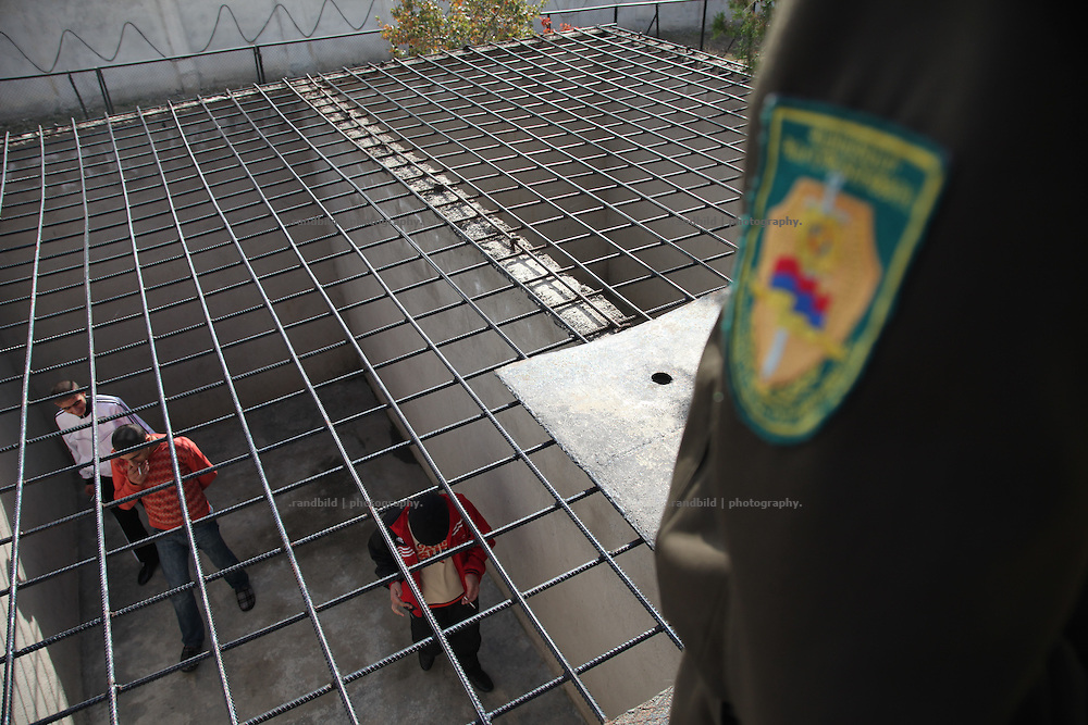 The Women and Youth Prison Abovian near the armenian capital Yerevan. Abovian, where about 200 criminal offenders are imprisoned, represents the most modern jail of Armenia, even many devlopements must be done to become western european standart. Picture: young offenders walking around an outside cage while getting observed by a guard.