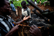 """Arrow boys"" look over the burnt home of a widow that was wounded during a recent LRA attack."