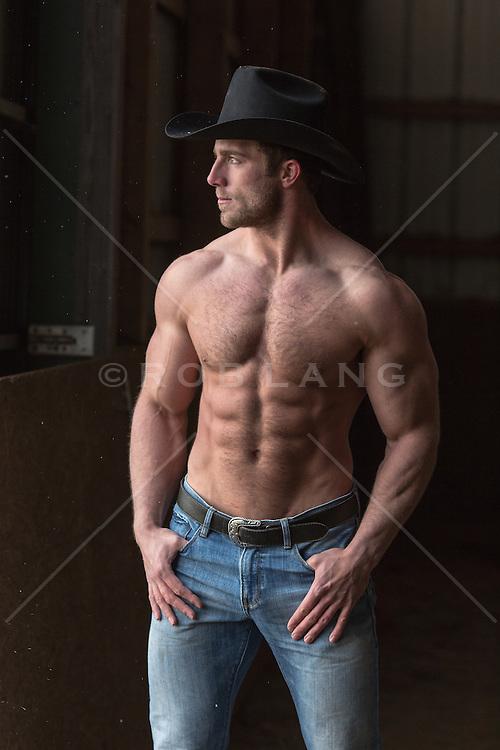 shirtless muscular cowboy in a barn