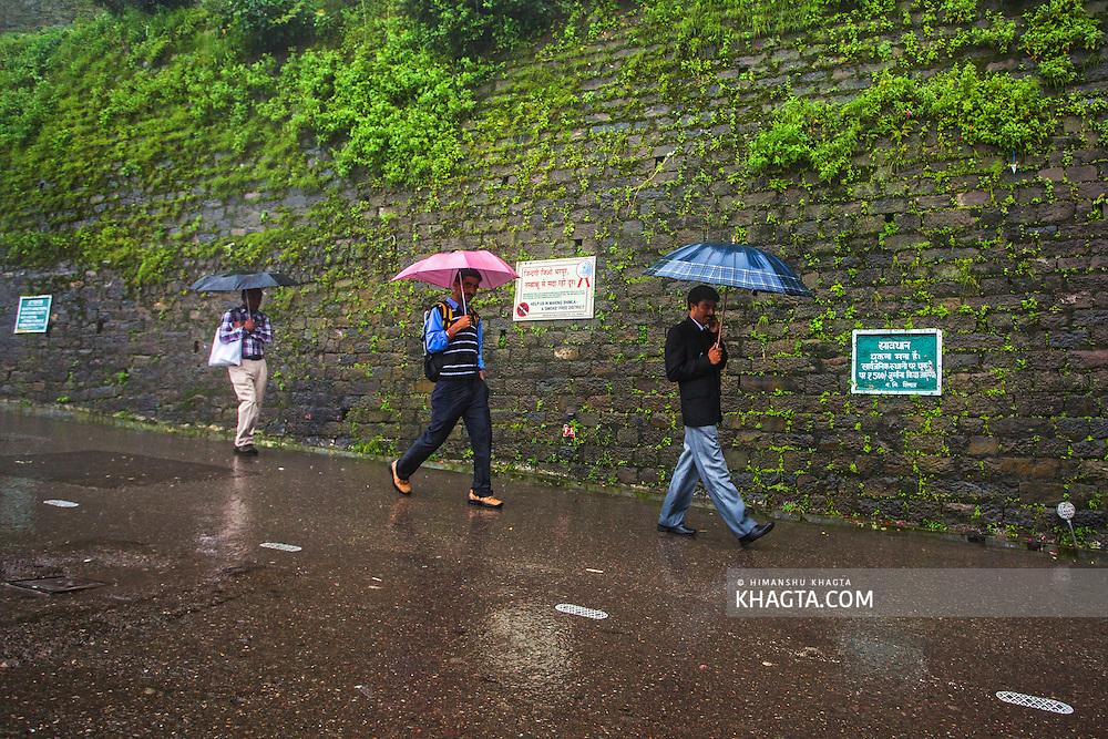 Three men walking with their umbrellas on the Mall Road of Shimla, Himachal Pradesh, India