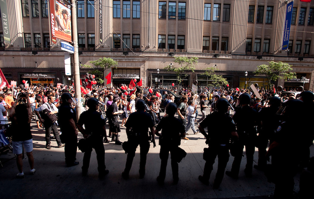 Police in riot gear look on as protestors march through the streets of Toronto, Canada, June 25, 2010 as the G8 leaders gather in Huntsville, Ontario. The G20 moves to Toronto on Saturday.<br /> AFP/GEOFF ROBINS/STR