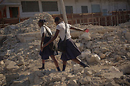 Port-au-Prince, HAITI, 22/03/2011: One year after the massive earthquake hit Haiti's capital, people try to recover their quotidian life, in the middle of a destructed city. Students in their way to school passes by ruins from the earthquake. (photo: Caio Guatelli)
