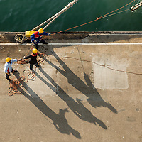 China, Hong Kong, Dockworkers tie up cruise ship in Tsim Sha Tsui on Kowloon side of Hong Kong Harbour on winter morning