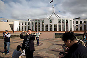 Australian Parliment House Canberra. Tourists on the aboriginal style Mosaic out the front of Parliament House.