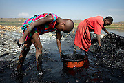 Young sisters work at their family owned salt pan, removing mud from the bed of the pan, at Lake Katwe.