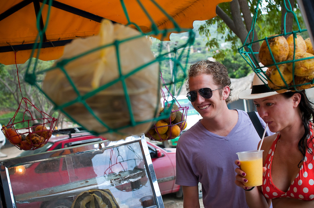 Joe DiMento, 27, and Emily Murphy DiMento, 28, from San Francisco, CA buy fresh mango juice from a street vendor while on their honeymoon in Taganga, Colombia.