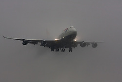 "January 3rd 2015, Heathrow Airport, London. Low cloud and rain provide ideal conditions to observe wake vortexes and ""fluffing"" as moisture condenses over the wings of landing aircraft. With the runway visible only at the last minute, several planes had to perform a ""go-round"", abandoning their first attempts to land. PICTURED: A British Airways Boeing 747 Jumbo Jet emerges from the low cloud moments before touchdown on Heathrow's runway 27L."