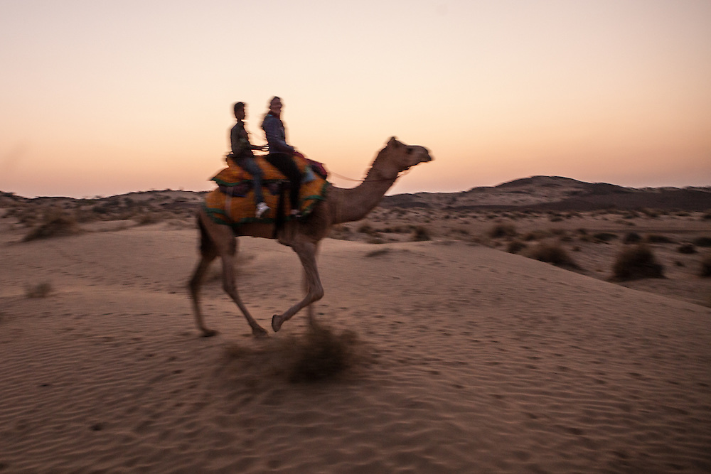 Two people riding a camel through the desert. Thar Desert, India.