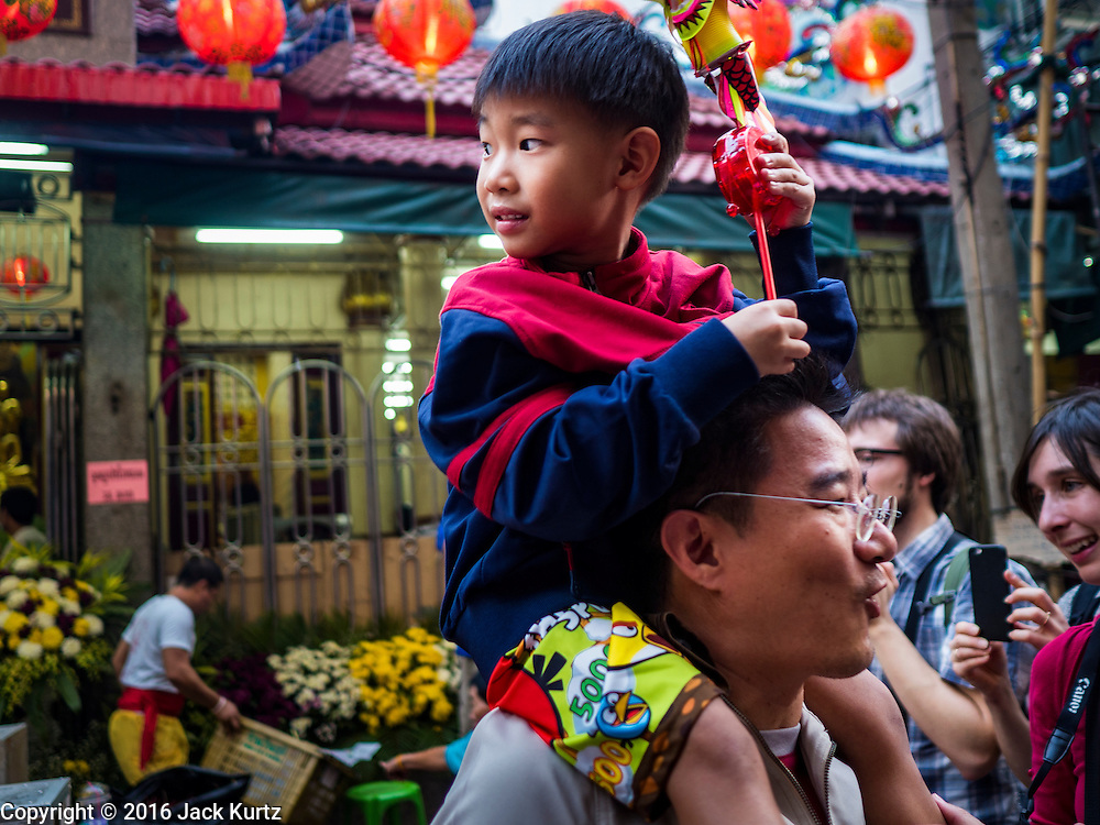 "08 FEBRUARY 2016 - BANGKOK, THAILAND: A boy perched on his father's shoulders watch lion dancers perform for Chinese New Year at a small Chinese shrine in Bangkok's Chinatown district, during the celebration of the Lunar New Year. Chinese New Year is also called Lunar New Year or Tet (in Vietnamese communities). This year is the ""Year of the Monkey."" Thailand has the largest overseas Chinese population in the world; about 14 percent of Thais are of Chinese ancestry and some Chinese holidays, especially Chinese New Year, are widely celebrated in Thailand.      PHOTO BY JACK KURTZ"
