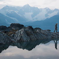 A man walks alone along the water at Harriman Fiord, Prince William Sound, Alaska