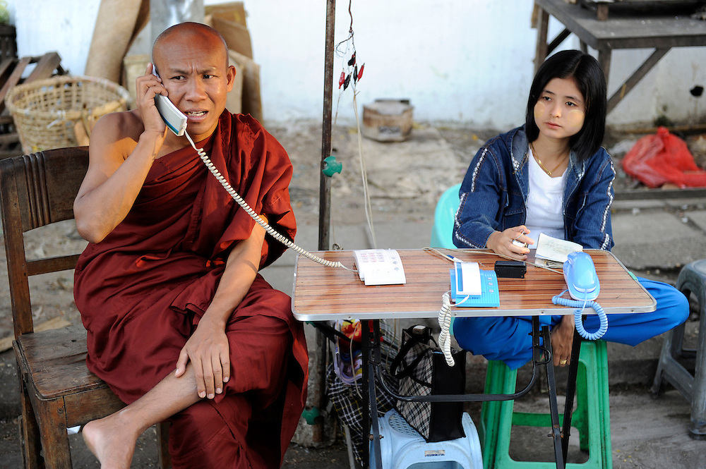 A Monk uses a telephone service to make a call, while the vendor keeps check as to how much time he has used up. Yangon (Rangoon) Myanmar (Burma) January 2012