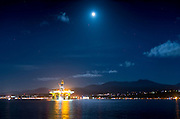 Alien spaceship? No, it's the 400 foot tall Polar Pioneer, an oil platform brought in from Asia piggybacked on a large ship, on its way to Seattle and maybe Alaska. It is temporarily in Port Angeles harbor, seen here from Ediz Hook under a full moon with the Olympic mountains behind. ©patrick downs