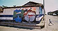 DEPARTMENT DE CHALATENANGO, EL SALVADOR- MAY 2000: A young boy runs across the street toward a building with a wall mural showing support for PCN, the National Conciliation Party,Partido de Conciliacion Nacional, who were the leading right-wing political party at the time of El Salvador's civil war against the left-wing FMLN, Farabundo Martí National Liberation Front, Frente Farabundo Martí para la Liberación Nacional.  (Photo by Robert Falcetti). .