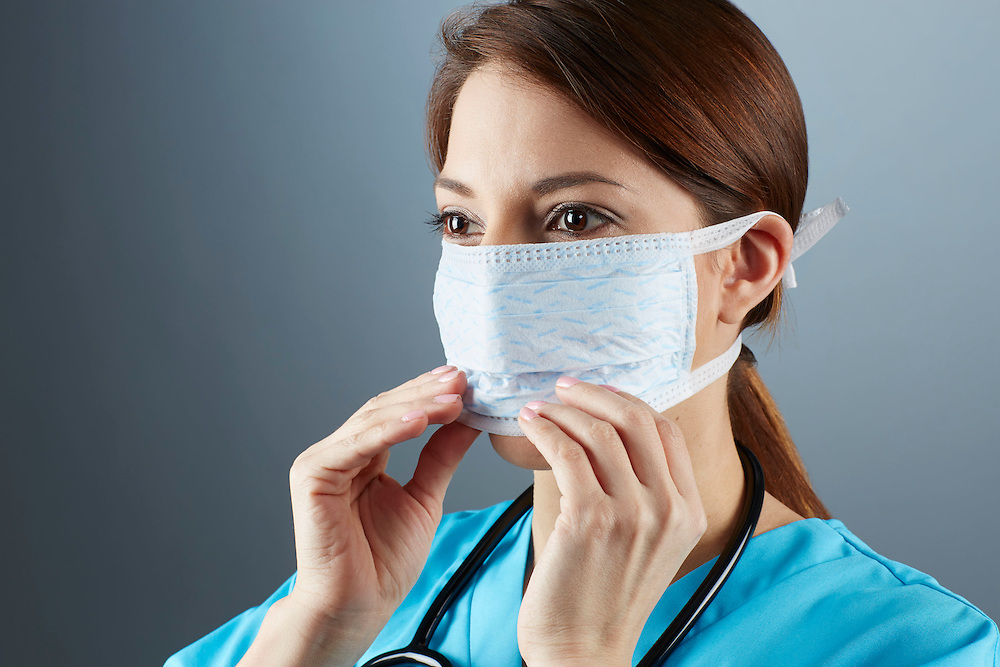 A portrait series representing the intense emotions that Doctors face.  A white female Doctor wearing a white surgical mask, stethoscope, and blue medical scrub suit shown.