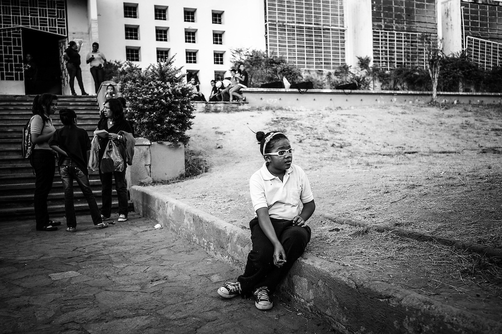 A girl waits to be picked up from her parents outside of the Sarria nucleo, of the El Sistema music program in Sarria, a  dangerous slum in Caracas, Venezuela.