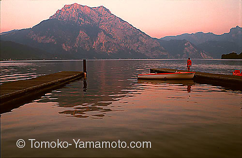 Traunstein, a rocky peak on the bank of Traunsee, Lake Traun, glows in red in sunset light.  This is a view of Traunstein seen from the pier in Altmuenster, Austria, a small lake-side town.  A red-colored small motorboat is at the pier with a boy in red shirt top.