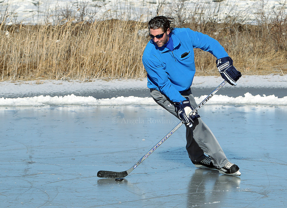 (Quincy, MA - 1/27/13) Chad Balog of Quincy skates with a puck on a frozen tidal pond in Quincy, Sunday, January 27, 2013. Staff photo by Angela Rowlings.