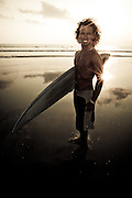 An Indonesian surfer poses before heading out for a sunset surf, Kuta Beach, Bali, Indonesia.