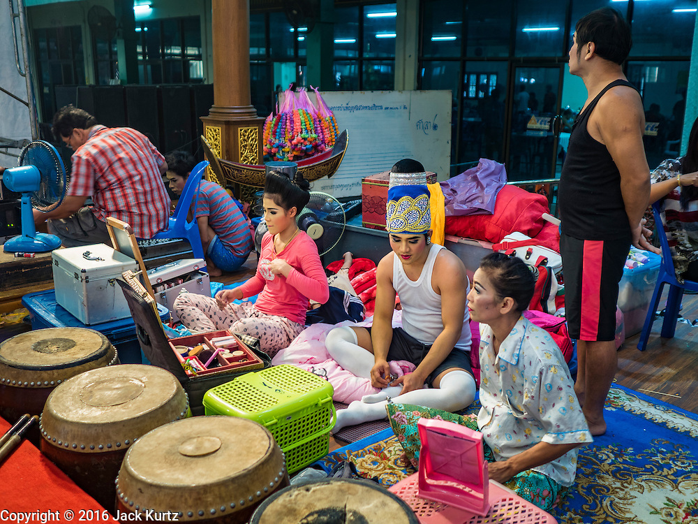 """30 JANUARY 2016 - NONTHABURI, NONTHABURI, THAILAND: Performers backstage before a """"likay"""" show at Wat Bua Khwan in Nonthaburi, north of Bangkok. Likay is a form of popular folk theatre that includes exposition, singing and dancing in Thailand. It uses a combination of extravagant costumes and minimally equipped stages. Intentionally vague storylines means performances rely on actors' skills of improvisation. Like better the known Chinese Opera, which it resembles, Likay is performed mostly at temple fairs and privately sponsored events, especially in rural areas. Likay operas are televised and there is a market for bootleg likay videos and live performance of likay is becoming more rare.     PHOTO BY JACK KURTZ"""