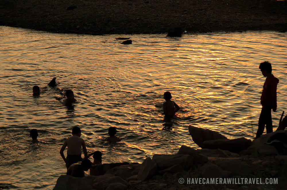 A group of boys swim in the waters of the Mekong River in Vientiane, Laos, as the sun sets in a hazy sky, creating golden afternoon colors.