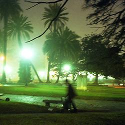 BUENOS AIRES, ARGENTINA: A man walks through a park in Buenos Aires, Argentina after dusk.  (Photo by Ami Vitale).