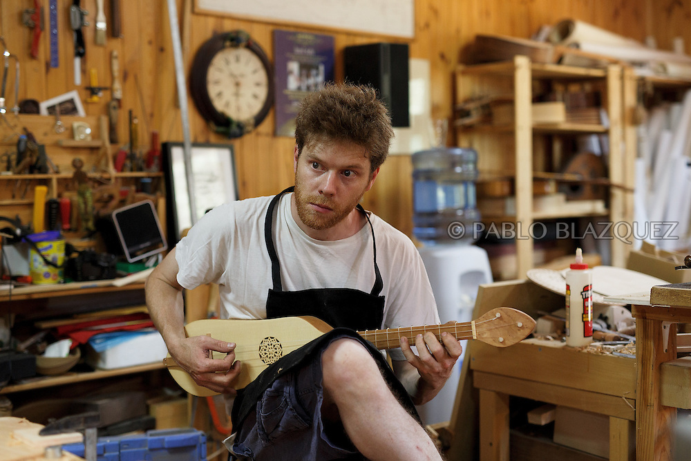 10/08/2016. Luthier Olivier Feraud plays a viol in a workshop on August 10, 2016 in Pelayos de la Presa, Madrid province, Spain. The Collegiate of Santa María la Mayor is a Romanesque architecture church built during the 12th and 13th centuries. Recents restorations of the Church discovered many details on its sculptures, and luthiers found the opportunity of recovering and to reproduce instruments showing on its North gate. (© Pablo Blazquez)