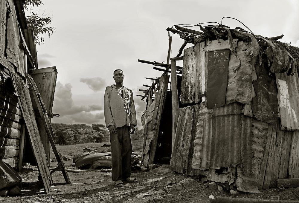 Batey 50, Dominican Republic- A Haitian sugarcane worker stands outside his small hut in the sugarcane workers village Batey 50. Many of the cane workers earn less than what the law allows according to a U.S. Department of Labor report issued 27 Sept 13. Dominican law sets the minimum wage for field workers in the sugar sector at 129 pesos ($3.08) per eight-hour workday, yet many workers claim they earn an average of $2.00 per 12-hour workday. Life in the worker's communities, known as bateyes is difficult, exacerbated by the lack of clean drinking water. These villages also often lack adequate housing, medical services, and other basic sanitary services. (Photo by Robert Falcetti)