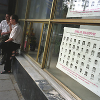 """Two men smoke near a police """"wanted criminals"""" poster in Tashkent, a city on the old Silk Road trading route. Uzbekistan is known as the more hardline of the Central Asian republics."""