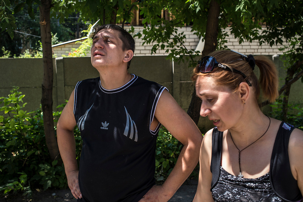 People look at an apartment building which was hit and damaged by artillery fire in the Oktyabrskaya neighborhood on Sunday, July 27, 2014 in Donetsk, Ukraine.