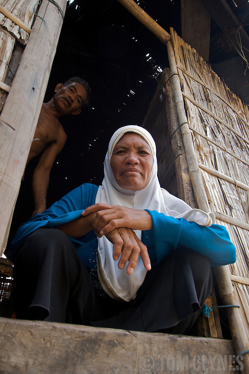 A woman in the doorway of her elevated house in Komodo Village, a Muslim fishing community in remote Komodo National Park in Indonesia. The park draws adventurous travelers hoping to see the carnivorous Komodo dragon (Varanus komodoensis), the world's largest monitor lizard. Several human fatailities have resulted from komodo dragon attacks in recent years.