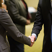 """""""Handshakes"""" - Angela Waksmunski, a staffing manager with Ajilon, a """"specialized"""" finance staffing and recruitment agency, greets unidentified job seekers at a job fair in Arlington, VA on Friday, Jan. 15, 2010."""