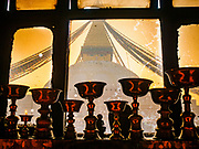 17 MARCH 2017 - KATHMANDU, NEPAL: Butter lamps and a soot covered window frame Boudhanath Stupa in Kathmandu. The stupa is the holiest site in Nepali Buddhism. It is also the center of the Tibetan exile community in Kathmandu. The Stupa was badly damaged in the 2015 earthquake but was one of the first buildings renovated.     PHOTO BY JACK KURTZ