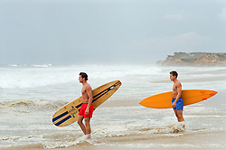 two handsome men entering the water to go surfing
