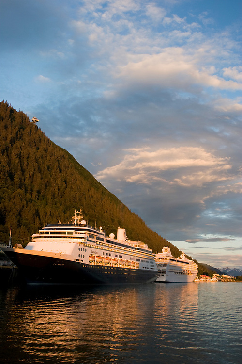 Two cruise ships await passengers at the dock in Juneau at sunset beneath the Mt. Roberts Tram